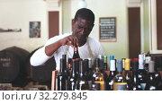 Купить «Confident male vintner choosing wine bottle on shelf rack and proffering to buy in modern wine shop», видеоролик № 32279845, снято 15 ноября 2019 г. (c) Яков Филимонов / Фотобанк Лори