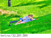 Купить «Russia, Samara, May 2019: a girl and a young student give lectures while lying on the grass in a park on a summer sunny day.», фото № 32281389, снято 1 июня 2019 г. (c) Акиньшин Владимир / Фотобанк Лори