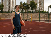 Купить «Male basketball player holds a ball, outdoor court», фото № 32282421, снято 13 июня 2019 г. (c) Tryapitsyn Sergiy / Фотобанк Лори