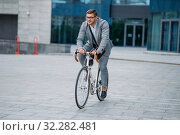 Businessman poses on bicycle at office building. Стоковое фото, фотограф Tryapitsyn Sergiy / Фотобанк Лори