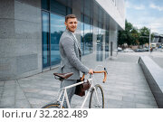 One businessman with briefcase cycling in downtown. Стоковое фото, фотограф Tryapitsyn Sergiy / Фотобанк Лори