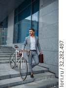 Businessman with bicycle comes down the stairs. Стоковое фото, фотограф Tryapitsyn Sergiy / Фотобанк Лори