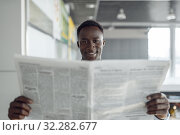 Ebony businessman with newspaper in office hallway. Стоковое фото, фотограф Tryapitsyn Sergiy / Фотобанк Лори