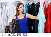 Купить «Girl choosing new clothes in showroom», фото № 32283325, снято 17 сентября 2018 г. (c) Яков Филимонов / Фотобанк Лори
