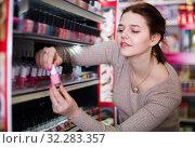 Купить «Pretty female searching for reliable nail polish», фото № 32283357, снято 21 февраля 2017 г. (c) Яков Филимонов / Фотобанк Лори