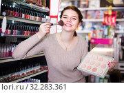 Купить «Young girl client is searching for reliable compact powder», фото № 32283361, снято 21 февраля 2017 г. (c) Яков Филимонов / Фотобанк Лори