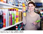 Купить «young woman customer deciding on hair care products in shop», фото № 32283365, снято 21 февраля 2017 г. (c) Яков Филимонов / Фотобанк Лори