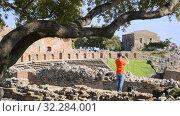 tourist makes a mobile photo of a spectacular view of the Greek amphitheater (2019 год). Редакционное видео, видеограф Ирина Мойсеева / Фотобанк Лори