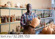 Afro-american artisan in apron having ceramics in store warehouse. Стоковое фото, фотограф Яков Филимонов / Фотобанк Лори