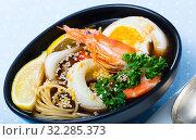 Купить «Photography of plate with spicy pan-Asian soup with squid, shrimp, egg noodles and sesame», фото № 32285373, снято 21 ноября 2019 г. (c) Яков Филимонов / Фотобанк Лори