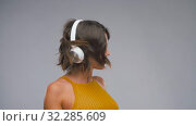 Купить «happy laughing young woman in headphones dancing», видеоролик № 32285609, снято 7 октября 2019 г. (c) Syda Productions / Фотобанк Лори