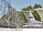 Купить «Transport aircraft stand at the airport fenced with barbed wire. Selective focus on the tail of the aircraft», фото № 32286021, снято 19 мая 2018 г. (c) Олег Белов / Фотобанк Лори