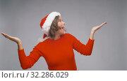 Купить «amazed woman in santa helper hat on christmas», видеоролик № 32286029, снято 7 октября 2019 г. (c) Syda Productions / Фотобанк Лори