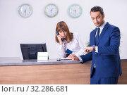 Купить «Young businessman at hotel reception», фото № 32286681, снято 13 июня 2019 г. (c) Elnur / Фотобанк Лори