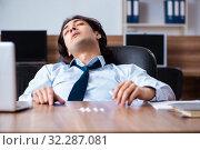 Купить «Young man having problems with narcotics at workplace», фото № 32287081, снято 24 апреля 2019 г. (c) Elnur / Фотобанк Лори