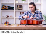 Купить «Young handsome repairman repairing cello», фото № 32287201, снято 4 апреля 2019 г. (c) Elnur / Фотобанк Лори