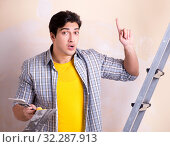 Купить «Young man applying plaster on wall at home», фото № 32287913, снято 15 марта 2018 г. (c) Elnur / Фотобанк Лори