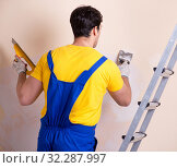 Купить «Young contractor employee applying plaster on wall», фото № 32287997, снято 15 марта 2018 г. (c) Elnur / Фотобанк Лори