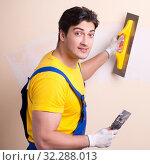 Купить «Young contractor employee applying plaster on wall», фото № 32288013, снято 15 марта 2018 г. (c) Elnur / Фотобанк Лори