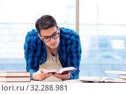 Купить «Student studying in the empty library with book preparing for ex», фото № 32288981, снято 19 января 2018 г. (c) Elnur / Фотобанк Лори