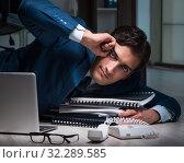 Купить «Businessman working overtime long hours late in office», фото № 32289585, снято 9 октября 2017 г. (c) Elnur / Фотобанк Лори