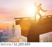 Купить «Businessman in uncertainty concept with broken bridge», фото № 32289689, снято 28 января 2020 г. (c) Elnur / Фотобанк Лори