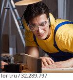 Купить «Worker working in repair workshop in woodworking concept», фото № 32289797, снято 11 августа 2017 г. (c) Elnur / Фотобанк Лори