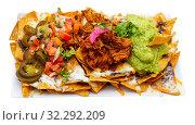 Купить «Corn chips nachos with homemade guacamole sauce, meat, cheese», фото № 32292209, снято 17 октября 2019 г. (c) Яков Филимонов / Фотобанк Лори