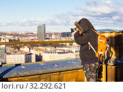 Photographer with big bag taking picture landmark the ancient european city from a high view point. Latvian Academy of Sciences. Sunny winter day. Riga, Europe, Baltic, Latvia. Travel photos concept. Стоковое фото, фотограф Алексей Ширманов / Фотобанк Лори