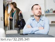 Купить «Frustrated man at table on background with woman leaving him», фото № 32295341, снято 15 января 2019 г. (c) Яков Филимонов / Фотобанк Лори