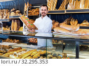 Купить «Man baker showing warm tasty bun in bakery», фото № 32295353, снято 26 января 2017 г. (c) Яков Филимонов / Фотобанк Лори