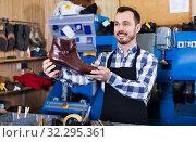 Купить «Male worker demonstrating repaired shoes in shoe», фото № 32295361, снято 2 февраля 2017 г. (c) Яков Филимонов / Фотобанк Лори