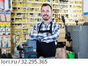 Купить «Happy worker showing his tools for making keys», фото № 32295365, снято 2 февраля 2017 г. (c) Яков Филимонов / Фотобанк Лори