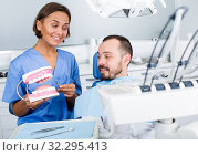 Купить «doctor in uniform is telling about hygiene of teeth in dental office», фото № 32295413, снято 10 июля 2017 г. (c) Яков Филимонов / Фотобанк Лори