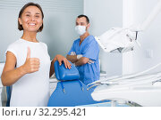 Купить «Girl is standing satisfied in dental office», фото № 32295421, снято 10 июля 2017 г. (c) Яков Филимонов / Фотобанк Лори