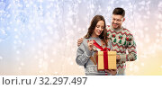 Купить «happy couple in christmas sweaters with gift box», фото № 32297497, снято 9 декабря 2018 г. (c) Syda Productions / Фотобанк Лори