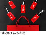 Купить «red shopping bag and tags with discount signs», фото № 32297649, снято 19 декабря 2018 г. (c) Syda Productions / Фотобанк Лори
