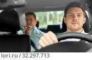 Купить «male taxi driver driving car with passenger», фото № 32297713, снято 25 августа 2019 г. (c) Syda Productions / Фотобанк Лори