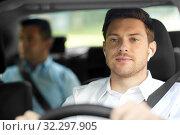 Купить «male driver with wireless earphones driving car», фото № 32297905, снято 25 августа 2019 г. (c) Syda Productions / Фотобанк Лори