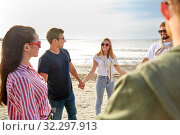 happy friends holding hands on summer beach. Стоковое фото, фотограф Syda Productions / Фотобанк Лори