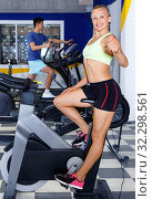 Fitness woman doing cardio workout cycling bike at gym. Стоковое фото, фотограф Яков Филимонов / Фотобанк Лори