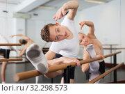 Graceful woman and young man pose in hall with ballet bar. Стоковое фото, фотограф Яков Филимонов / Фотобанк Лори