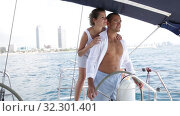 Купить «Young loving couple standing at yacht wheel enjoying sea trip along coast of Barcelona on sunny day», видеоролик № 32301401, снято 30 июля 2019 г. (c) Яков Филимонов / Фотобанк Лори
