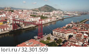 Купить «Aerial view of Vizcaya bridge over the river and cityscape at Portugalete, Spain», видеоролик № 32301509, снято 16 июля 2019 г. (c) Яков Филимонов / Фотобанк Лори