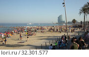 Купить «Beach with many people resting at Barcelona seaside in Catalonia, Spain», видеоролик № 32301577, снято 29 июня 2019 г. (c) Яков Филимонов / Фотобанк Лори
