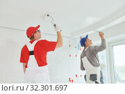 Two painter workers with roller painting ceiling surface into white. Стоковое фото, фотограф Дмитрий Калиновский / Фотобанк Лори