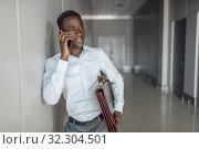Businessman talking by phone in office hallway. Стоковое фото, фотограф Tryapitsyn Sergiy / Фотобанк Лори