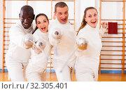 Купить «Smiling fencers posing with foils together at fencing room», фото № 32305401, снято 11 июля 2018 г. (c) Яков Филимонов / Фотобанк Лори