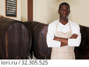 male winemaker or seller standing near wooden barrels in wine shop. Стоковое фото, фотограф Яков Филимонов / Фотобанк Лори