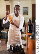 Купить «Smiling salesman in apron proposing wine in bottles in winery shop», фото № 32305553, снято 1 августа 2019 г. (c) Яков Филимонов / Фотобанк Лори